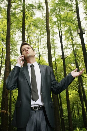 Businessman talking on the phone in the forest photo