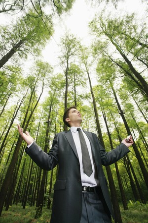 environment issues: Businessman with mobile phone in the forest