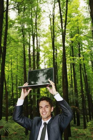 Businessman holding up a laptop Stock Photo - 8149348