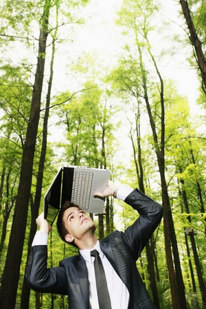 Businessman shielding his head with a laptop Stock Photo - 8149392