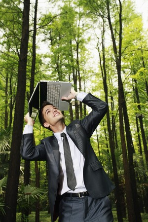 south western european descent: Businessman shielding his head with a laptop