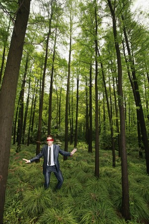 Businessman with blindfold walking aimlessly in the forest Stock Photo - 8149500