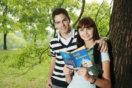 Man and woman reading book outdoors Stock Photo - 8149324
