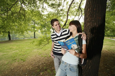Man and woman reading book outdoors