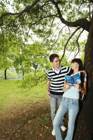 Man and woman reading book outdoors Stock Photo - 8149478