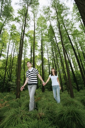 south eastern european descent: Man and woman holding hands in the forest
