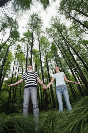 Man and woman holding hands in the forest photo