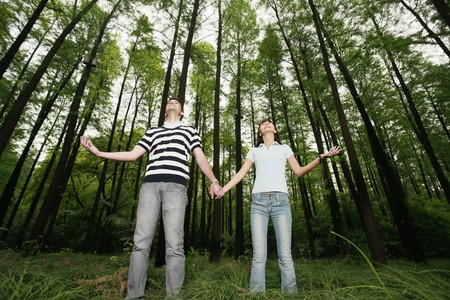 south western european descent: Man and woman holding hands in the forest