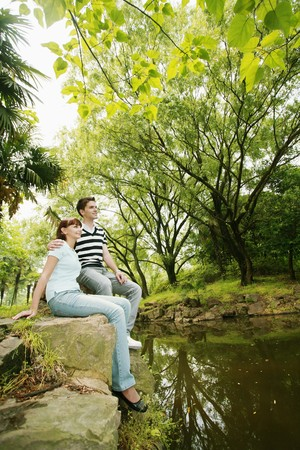 Man and woman sitting on the rocks Stock Photo - 8149471