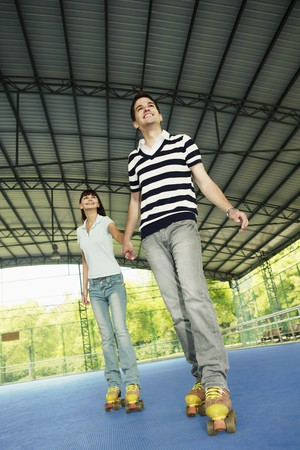 Man and woman holding hands while roller skating together Stock Photo - 8149329