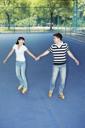 south western european descent: Man and woman holding hands while roller skating together