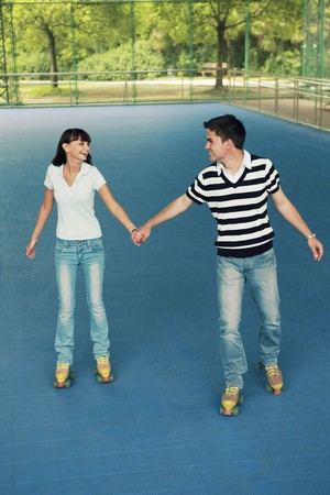 south eastern european descent: Man and woman holding hands while roller skating together