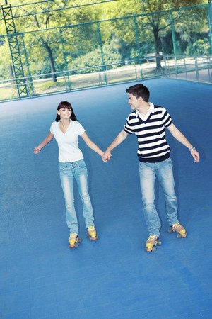Man and woman holding hands while roller skating together
