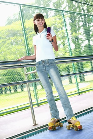 Woman with roller skates text messaging on the phone Stock Photo