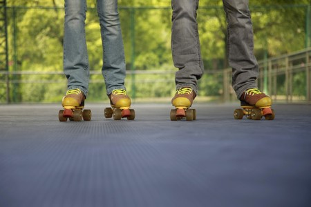 south eastern european descent: Man and woman roller skating together Stock Photo