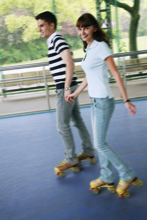 south eastern european descent: Man and woman holding hands while roller skating
