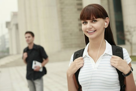 Woman with backpack listening to music on portable MP3 player Stock Photo - 8148637