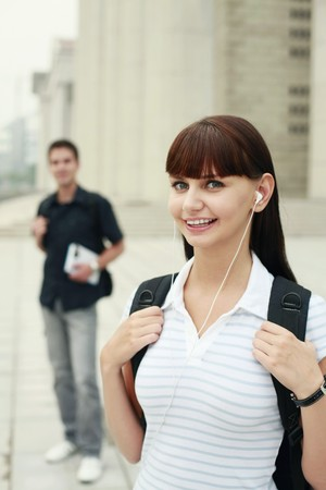 south western european descent: Woman with backpack listening to music on portable MP3 player Stock Photo