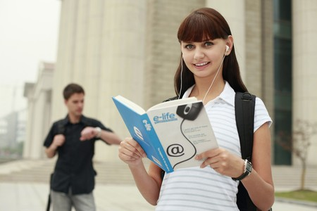 Woman reading book while listening to music on portable MP3 player photo