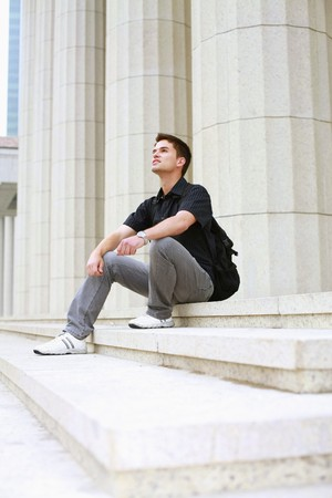 south western european descent: Man with backpack sitting on stairs