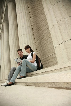 Man and woman sitting on stairs reading book Stock Photo