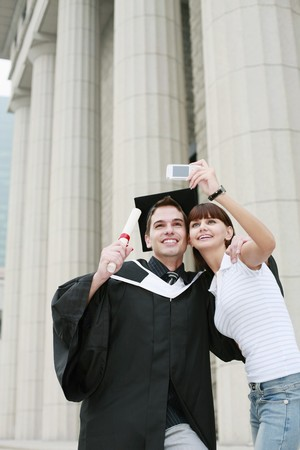 Woman taking picture with man in graduation gown photo