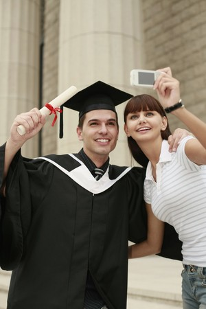 Woman taking picture with man in graduation gown Stock Photo