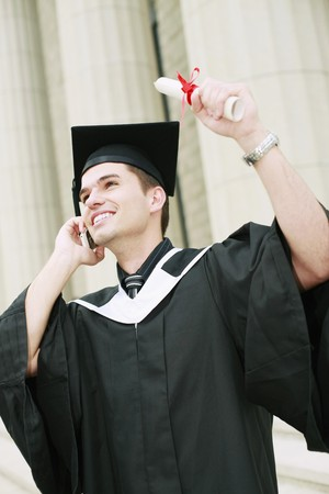 Graduate talking on the phone while holding up his scroll photo