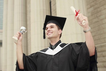 Graduate holding up his trophy and scroll photo