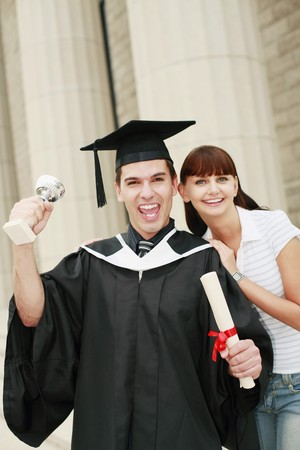 Graduate with trophy and scroll posing with woman photo