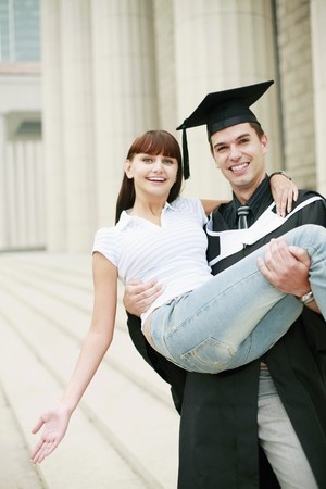 south eastern european descent: Man in graduation gown carrying woman in his arms Stock Photo