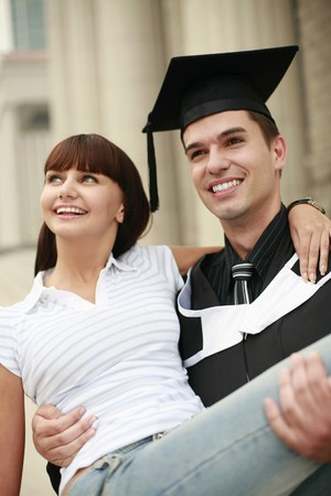 Man in graduation gown carrying woman in his arms photo