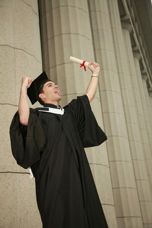 south western european descent: Graduate holding up his scroll and screaming Stock Photo