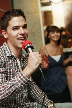 south eastern european descent: Man singing in karaoke bar