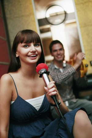 south western european descent: Woman singing in karaoke bar