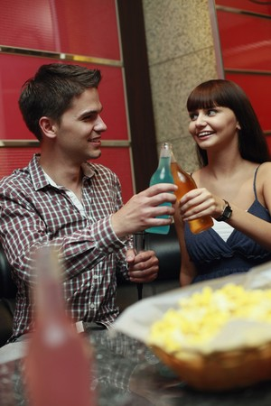 Man and woman toasting drinks photo