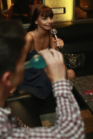 south eastern european descent: Woman singing into microphone, man drinking
