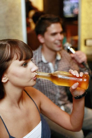 south eastern european descent: Woman drinking, man singing in the background
