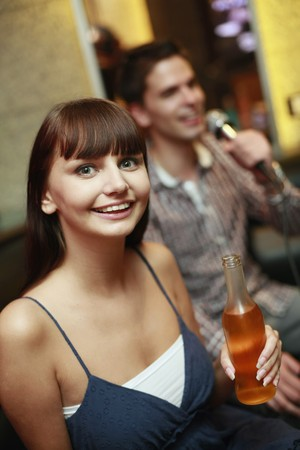 south eastern european descent: Woman holding bottled drink, man singing in the background
