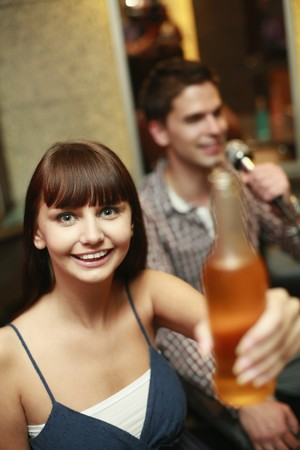 Woman holding bottled drink, man singing in the background photo