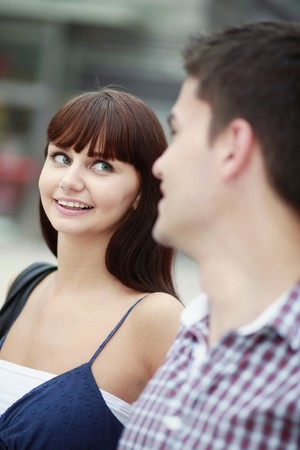 south eastern european descent: Man and woman smiling while looking at each other Stock Photo