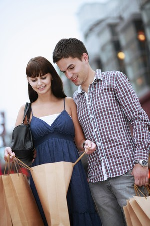 Man and woman looking into shopping bag Stock Photo - 8149365