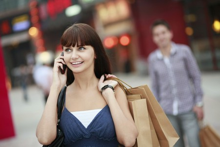 south eastern european descent: Woman with shopping bags talking on the phone Stock Photo