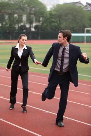Businesswoman passing baton to businessman photo