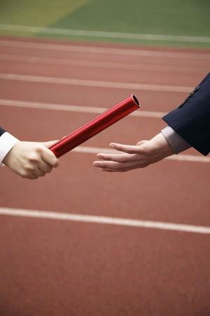 relay baton: Businesswoman passing baton to businessman