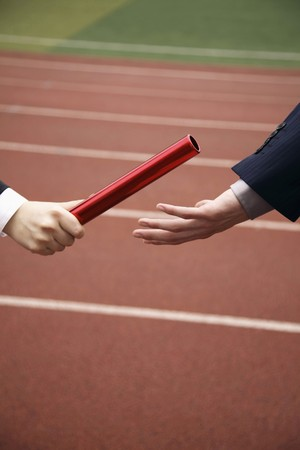 relay: Businesswoman passing baton to businessman
