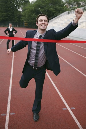 Businessman crossing the finishing line photo