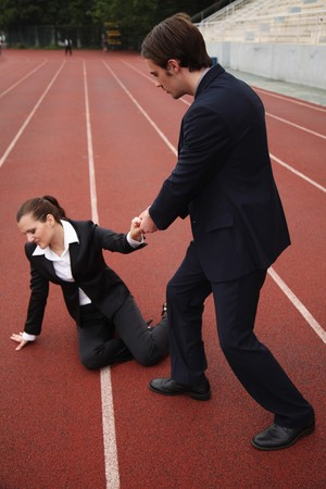 Businessman helping fallen businesswoman Stock Photo - 8148771