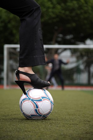 Businesswoman standing on football with businessman as the goal keeper Stock Photo - 8148374