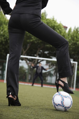 Businesswoman standing on football with businessman as the goal keeper photo
